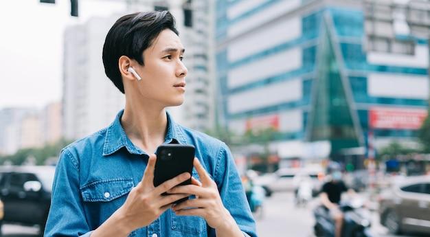 Jeune homme asiatique marchant et à l'aide de smartphone dans la rue