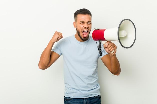 Jeune homme asiatique métisse tenant un mégaphone applaudissant insouciant et excité