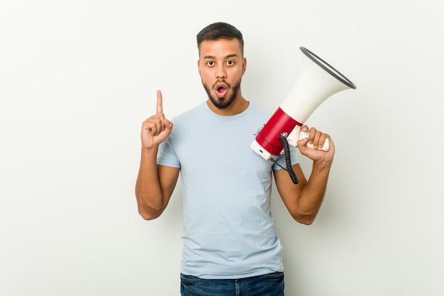 Jeune homme asiatique métisse tenant un mégaphone ayant une excellente idée, concept de créativité.
