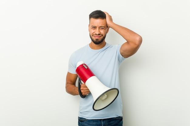 Jeune homme asiatique métisse tenant un mégaphone étant choqué, elle s'est souvenue d'une réunion importante.