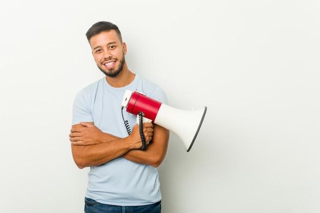 Jeune homme asiatique métisse tenant un mégaphone souriant confiant avec les bras croisés.