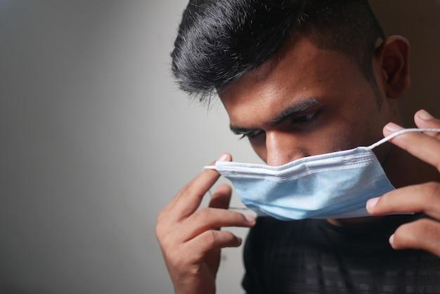 Jeune homme asiatique mettant un masque chirurgical à l'intérieur