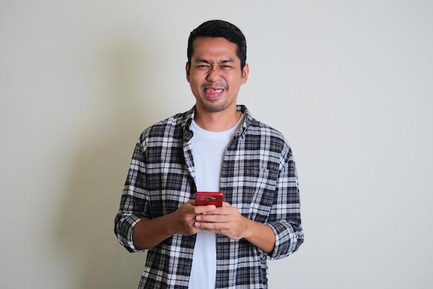 Jeune homme asiatique montrant une expression de visage stupide tout en envoyant des sms sur son téléphone portable