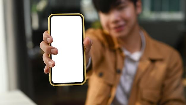 Jeune homme asiatique montrant un téléphone intelligent avec écran vide.