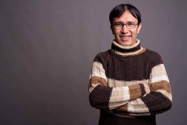 Jeune homme asiatique nerd portant un pull à col roulé contre un mur gris