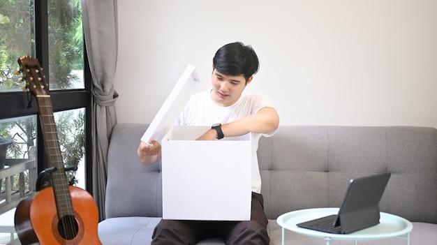 Jeune homme asiatique ouvrant une boîte-cadeau alors qu'il était assis sur un canapé.
