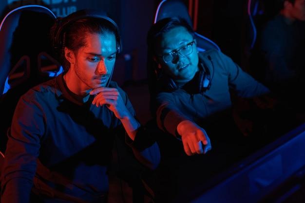Jeune homme asiatique pointant sur l'écran de l'ordinateur et parler à son ami pendant leur partie en club informatique
