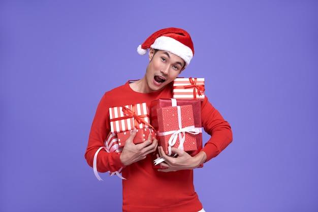 Jeune homme asiatique portant bonnet de noel et tenant la pile de cadeaux.