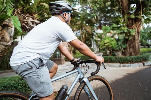 Jeune homme asiatique portant des casques de vélo lors de la conduite à vélo