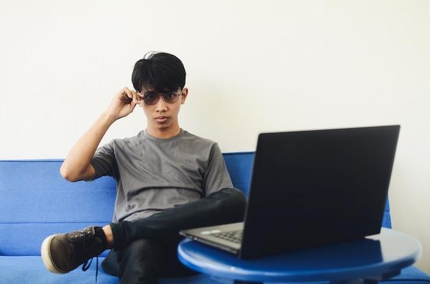 Jeune homme asiatique portant une chemise en frêne devant l'ordinateur portable assis sur le canapé