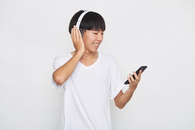 Jeune homme asiatique portant des écouteurs à partir d'un smartphone sur blanc