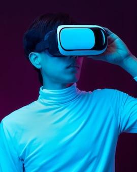 Jeune homme asiatique portant des lunettes de réalité virtuelle regardant une vidéo à 360 degrés en néon, concept technologique.