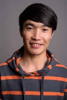Jeune homme asiatique portant un sweat à capuche rayé contre un mur gris