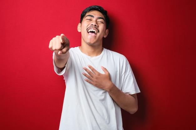 Jeune homme asiatique portant un t-shirt blanc debout sur fond rouge se moquant de vous, pointant le doigt vers la caméra avec la main sur le corps, expression de honte