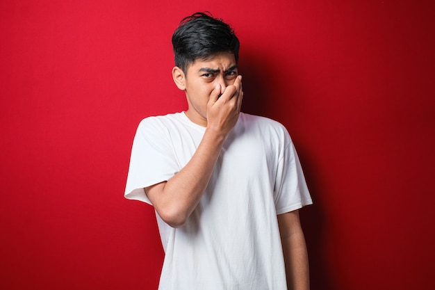 Jeune homme asiatique portant un t-shirt blanc sur fond rouge sentant quelque chose de puant et dégoûtant, odeur intolérable, retenant son souffle avec les doigts sur le nez. mauvaise odeur