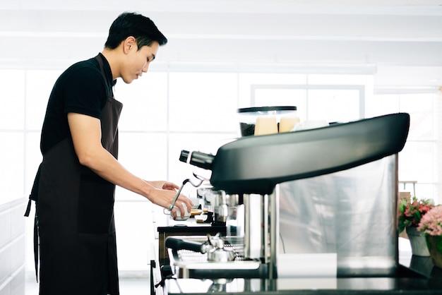 Jeune homme asiatique portant un tablier préparant une tasse de café et se tenant à l'intérieur du comptoir à café.