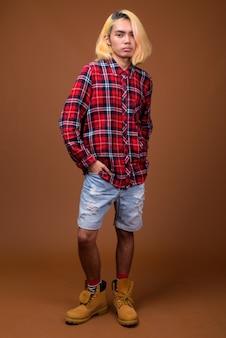 Jeune homme asiatique portant des vêtements élégants sur fond marron