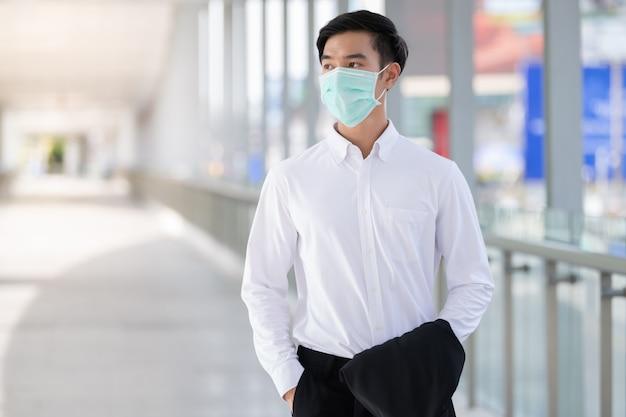Jeune homme asiatique porter un masque facial médical pour la protection des coronavirus, covid-19 et pm2.5 en ville urbaine