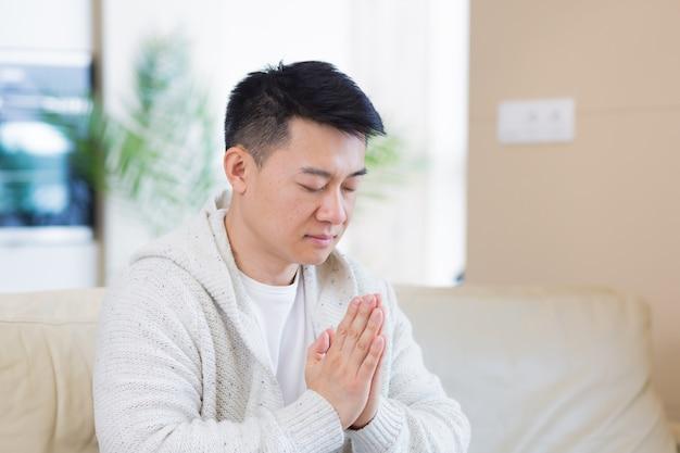 Jeune homme asiatique priant seul à la maison