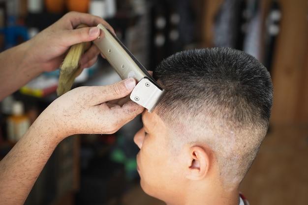 Jeune homme asiatique qui a les cheveux gris se fait couper les cheveux avec une tondeuse électrique par un coiffeur professionnel en salon de coiffure.