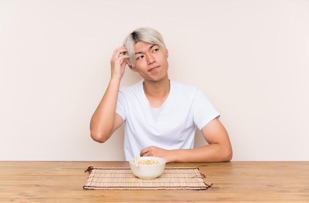 Jeune homme asiatique avec des ramen dans une table ayant des doutes et avec une expression du visage confuse