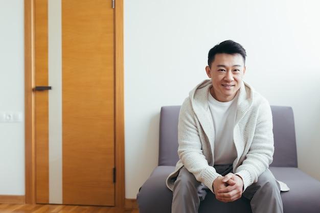 Un jeune homme asiatique a reçu une bonne nouvelle assis et souriant dans la salle d'attente pour les résultats des entretiens ou des tests à la clinique