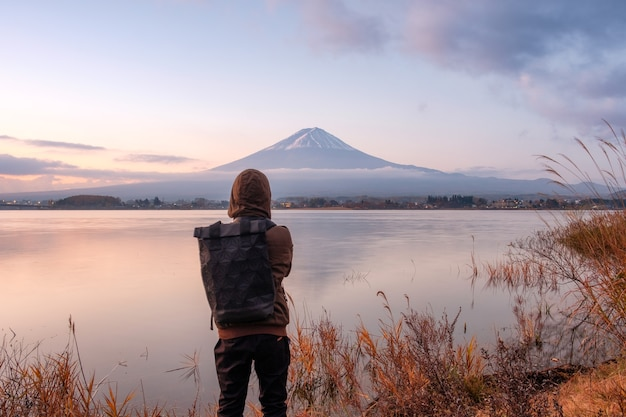 Un jeune homme asiatique regarde le mont fuji sur le lac kawaguchiko au matin