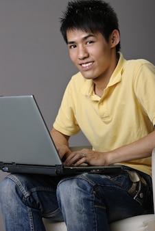 Jeune homme asiatique s'asseoir sur une chaise et utiliser un ordinateur portable