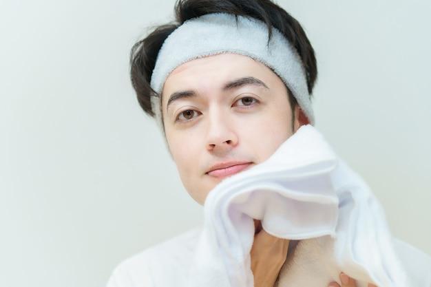 Jeune homme asiatique s'essuyant le visage avec une serviette