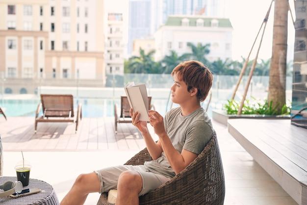 Un jeune homme asiatique se détend près de la piscine extérieure avec un livre dans les mains.