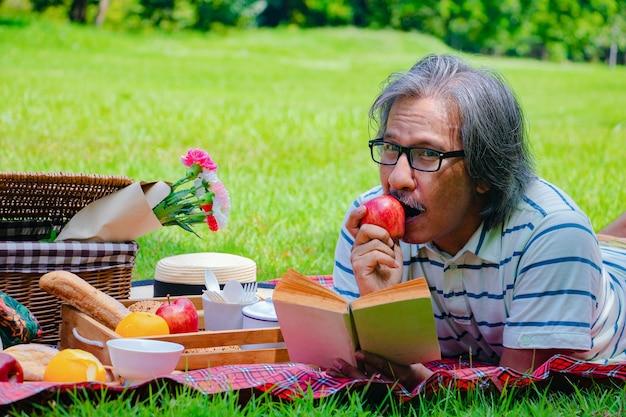 Jeune homme asiatique se détendre dans le parc. dans la matinée, il lit un livre avec application rouge