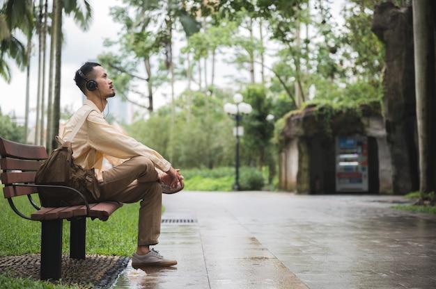 Un jeune homme asiatique se détendre et se détendre en écoutant de la musique avec un casque dans le parc. bonne sensation de la journée ensoleillée au jardin pendant les vacances.