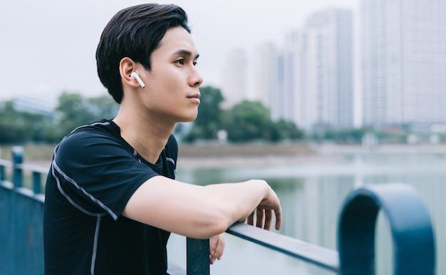 Jeune homme asiatique se repose après la séance d'entraînement