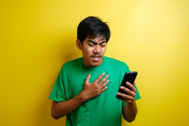 Jeune homme asiatique séduisant lisant des textos en discutant sur son téléphone, mauvaise nouvelle, expression de pleurs tristes sur fond jaune