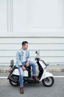 Jeune homme asiatique sérieux dans des vêtements de denim se reposant sur le cyclomoteur blanc contre le bâtiment moderne et regardant dans la distance