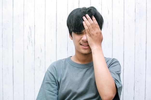 Jeune homme asiatique souffrant de fortes douleurs oculaires ou ayant des migraines