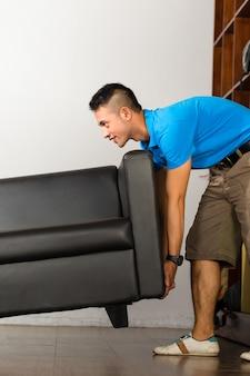 Jeune homme asiatique soulevant un canapé