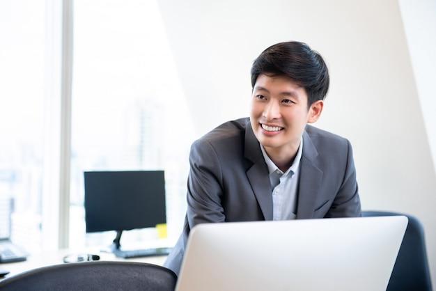 Jeune homme asiatique souriant au bureau