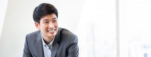 Jeune homme asiatique souriant sur fond de bannière de bureau blanc