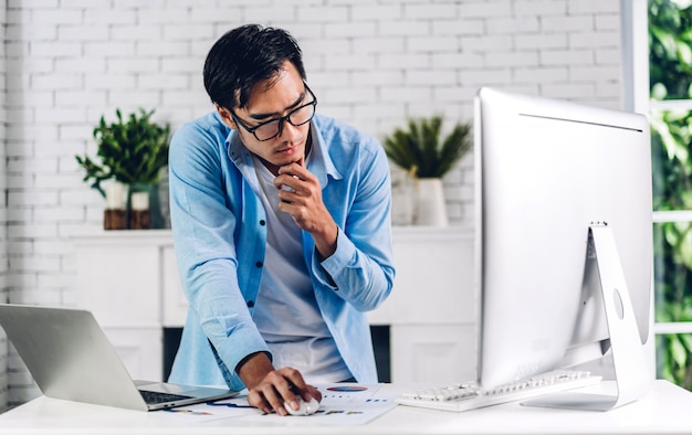 Jeune homme asiatique souriant souriant créatif relaxant à l'aide d'un ordinateur de bureau et d'une vidéoconférence réunissant un chat en ligne à la maison. travail à domicile concept