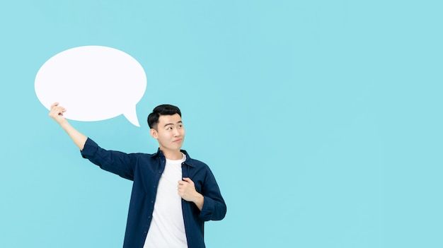 Jeune homme asiatique souriant tenant la bulle de dialogue vide et la pensée
