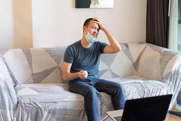 Jeune homme asiatique stressé avec masque ayant mal de tête à la maison en quarantaine