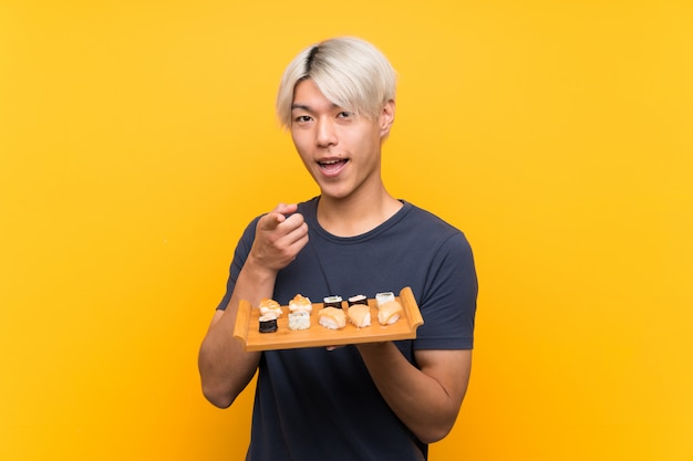 Jeune homme asiatique avec sushi sur doigt isolé points jaunes à vous