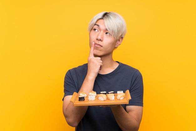 Jeune homme asiatique avec sushi sur jaune isolé, pensant une idée