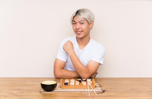 Jeune homme asiatique avec sushi à une table célébrant une victoire