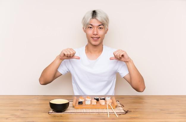 Jeune homme asiatique avec sushi à une table fier et satisfait