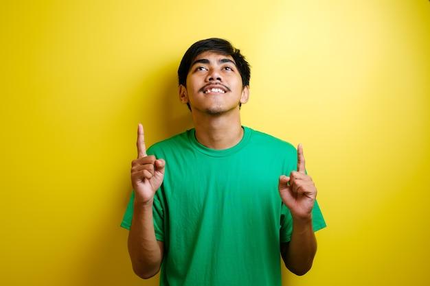 Un jeune homme asiatique en t-shirt vert avait l'air heureux de penser et de lever les yeux, ayant une bonne idée. portrait de la moitié du corps sur fond jaune avec espace de copie