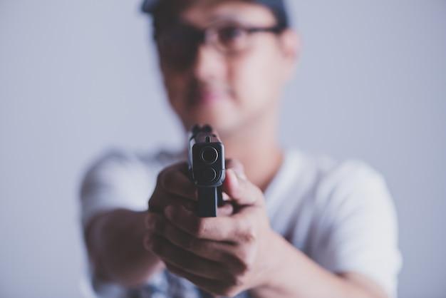 Jeune homme asiatique tenant une arme à feu visant à l'arme à feu