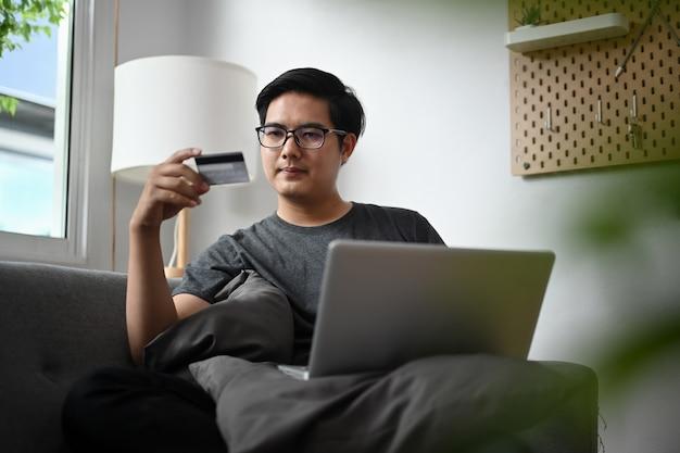 Jeune homme asiatique tenant une carte de crédit et utilisant un ordinateur portable pour faire du shopping en ligne dans le salon.