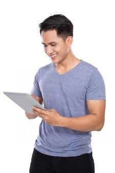 Jeune homme asiatique tenant un ordinateur tablette à écran tactile numérique o